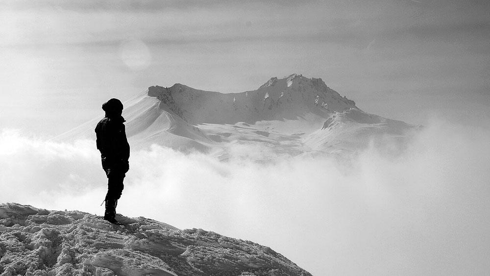Човек на върха на заснежена планина наблюдава пайзажа