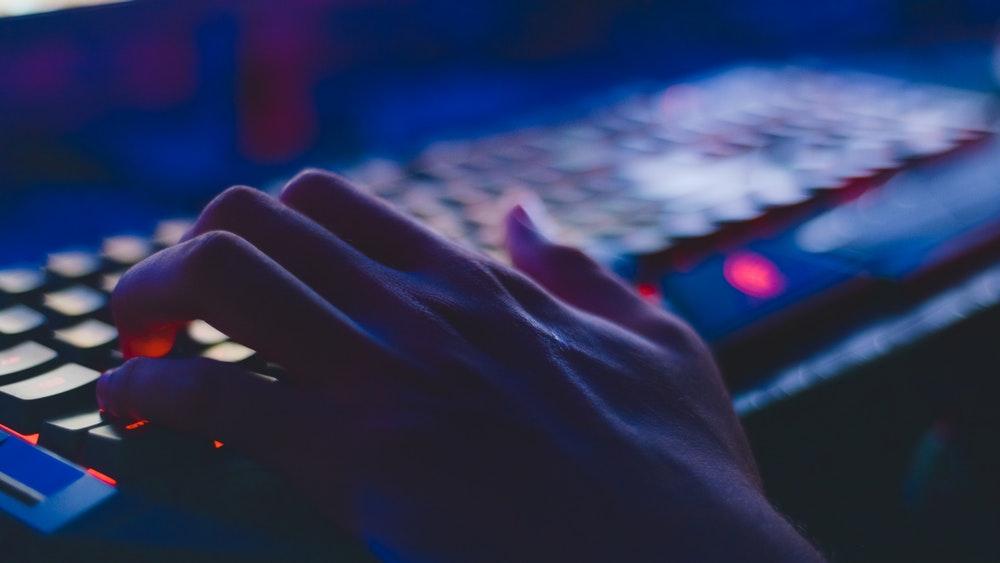 Геймър пишещ по клавиатура с подсветка
