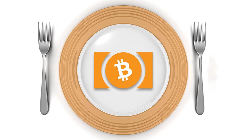 На снимката: символът на биткоин положен в чиния, с по вилица от всяка страна