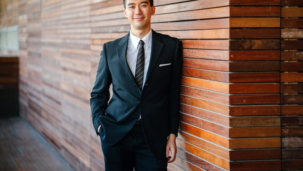 Усмихнат мъж облегнат на стена и облечен в костюм