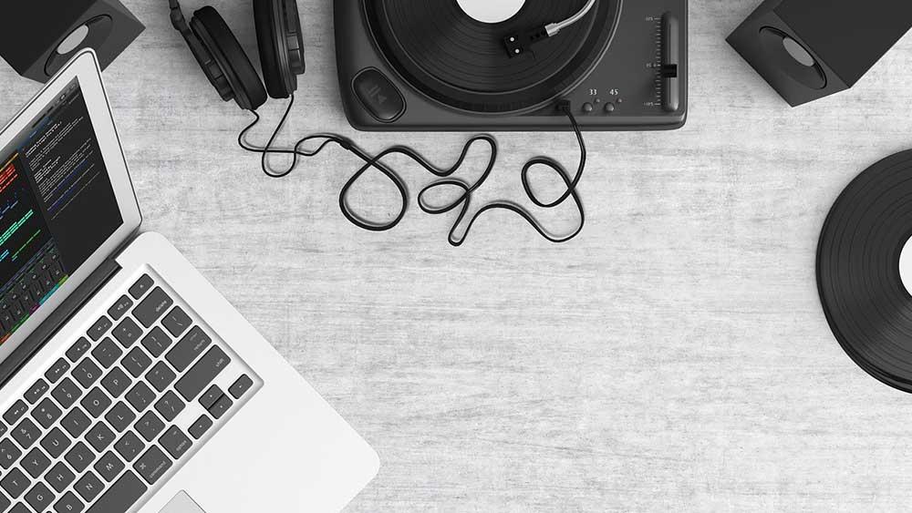 Снимка на грамофон, слушалки, грамофонна плоча и лаптоп на бюро