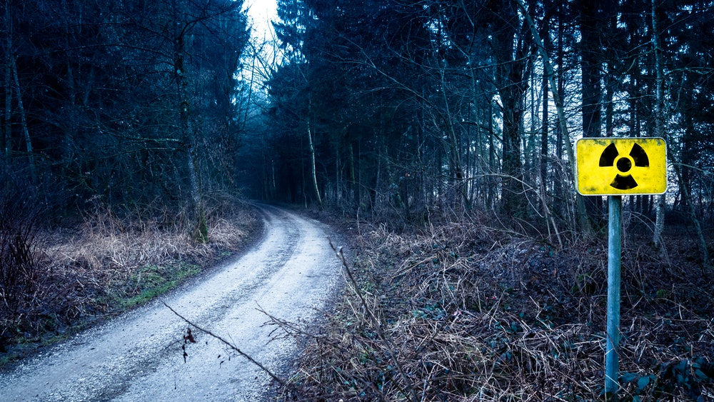 Горски път с жълта табела, предупреждаваща за токсични отпадъци