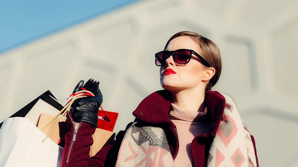 Облечена стилно жена, носеща покупките си в ръка
