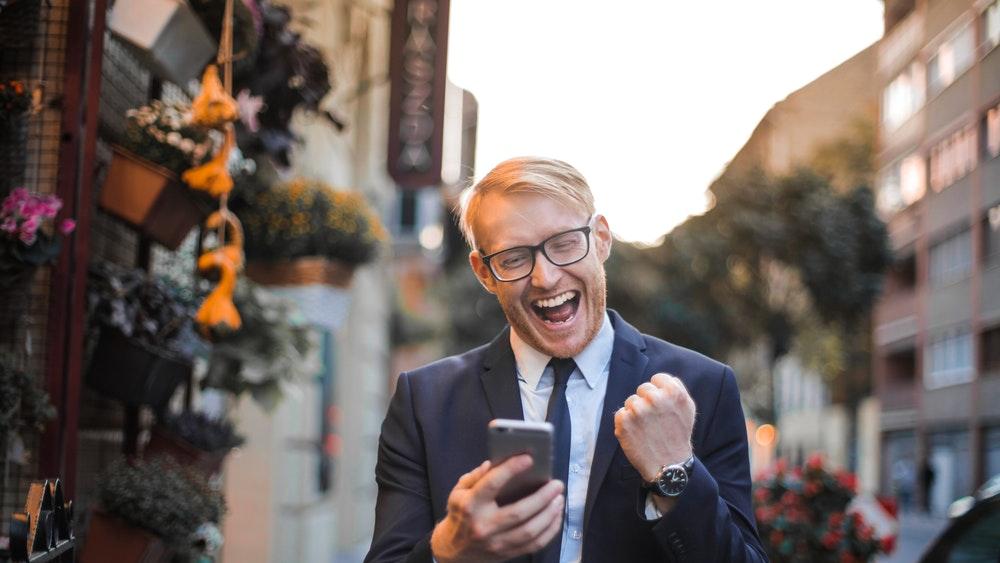 Р азхождащ се по улица щастлив костюмиран мъж