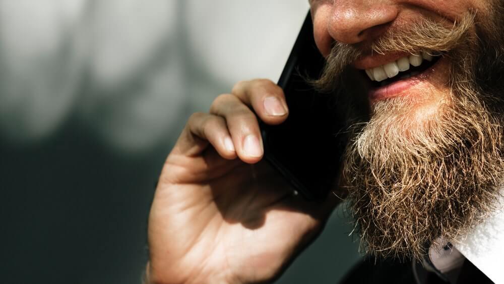 Мъж с брада разговаря по телефона