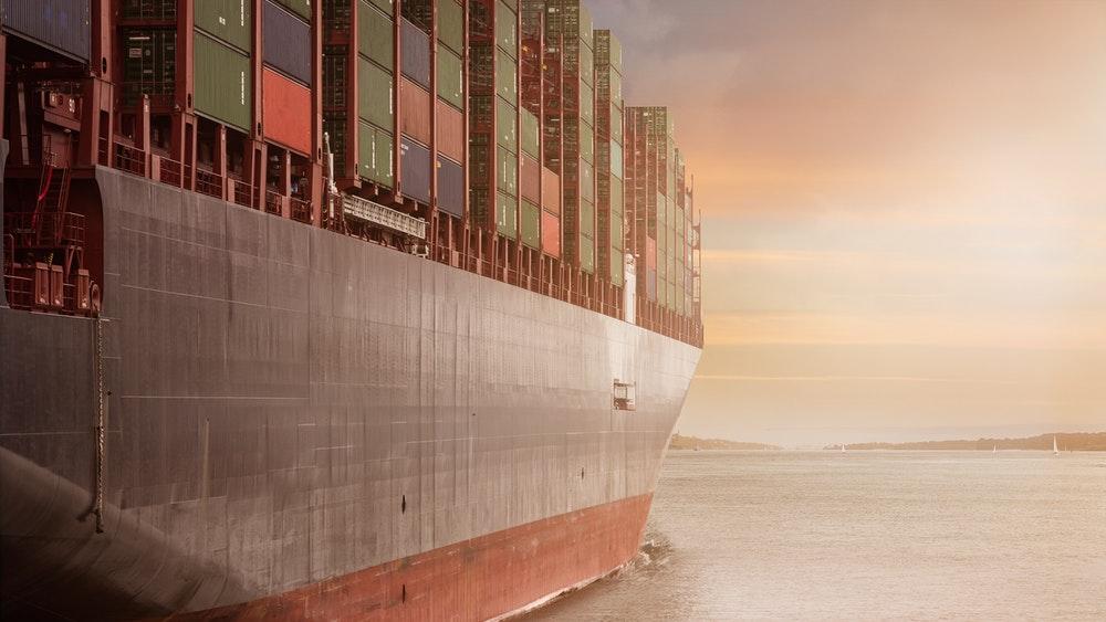 Тежкотоварен кораб, превозващ контейнери на фона на залез