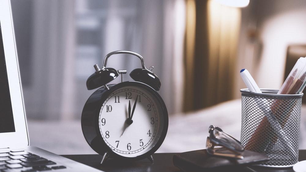 Снимка на аналогов будилник върху бюро