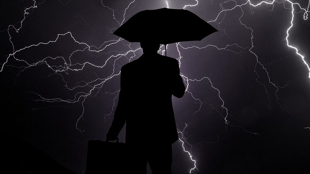 Picture of person holding an umbrella over lightning-lit sky.