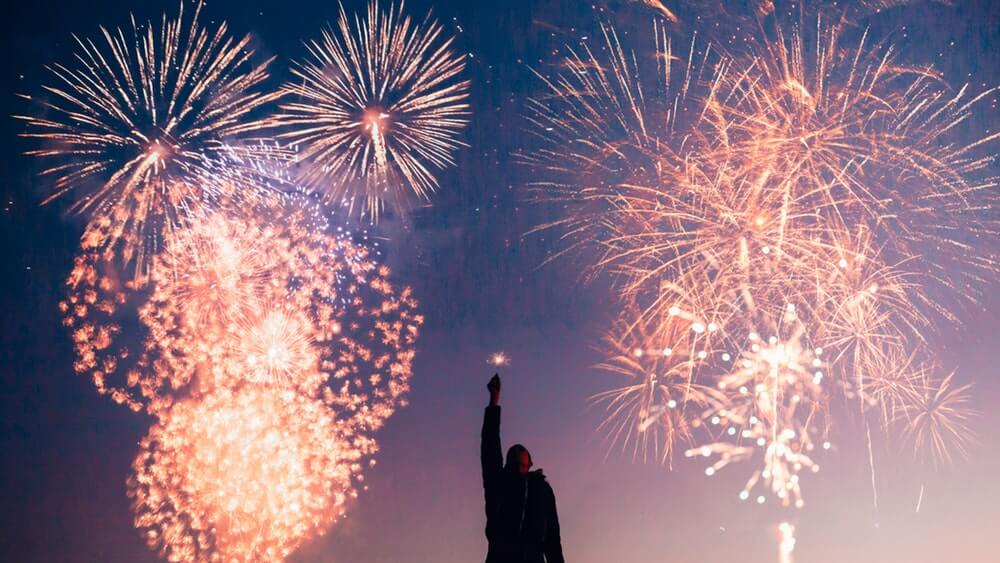 A man pointing towards fireworks-lit night sky.