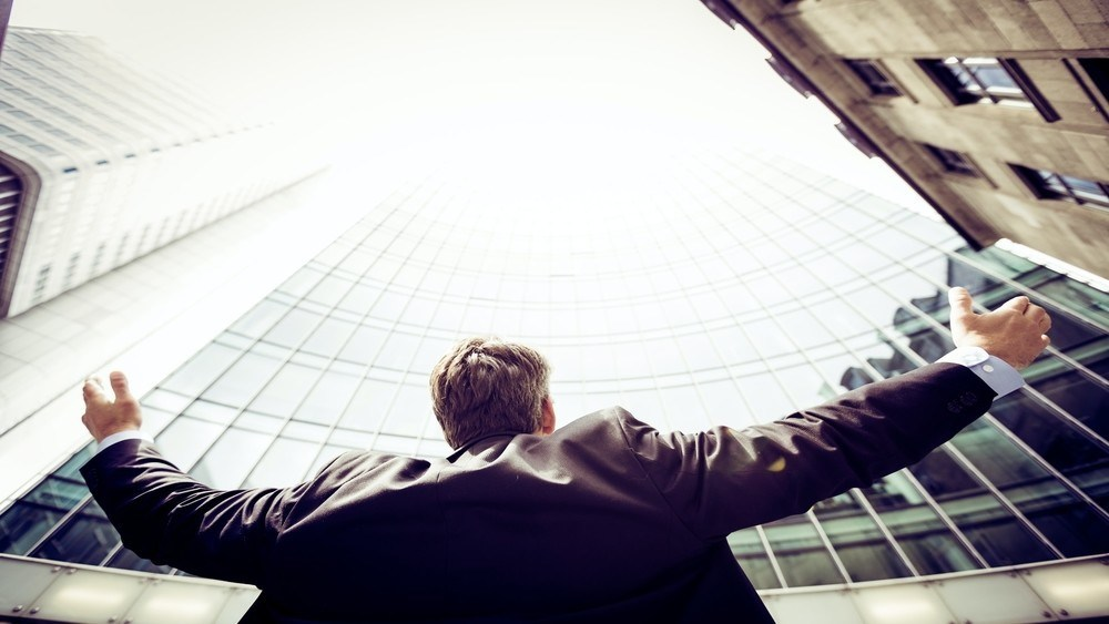 Picture of a man in suit looking up at a glass building