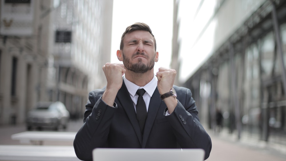 Man in business suit cheering at laptop screen